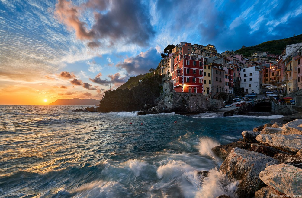 An unbelievable sunset in Riomaggiore as the waves crash on the rocky coastline.