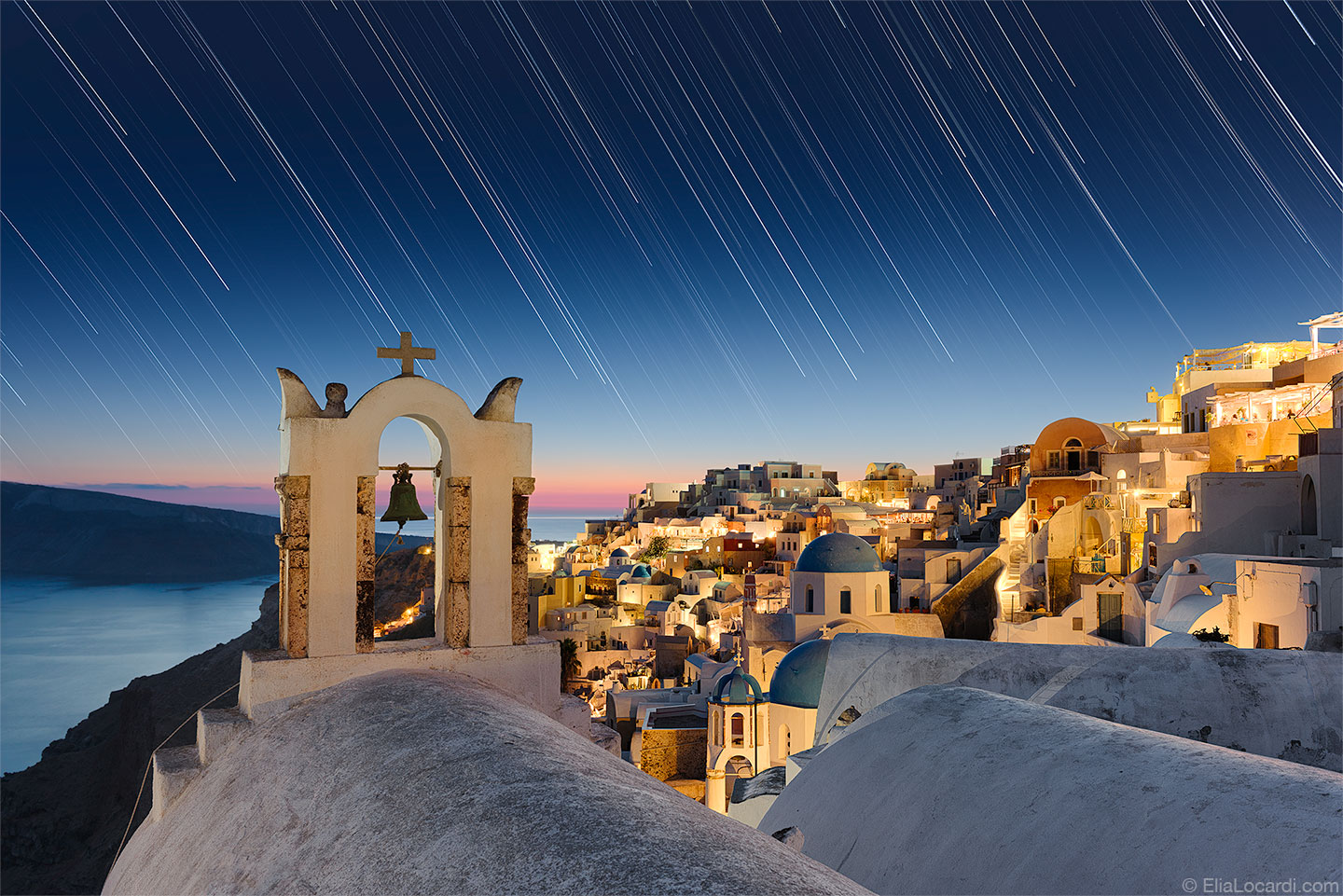 As the stars dance above the enchanting town of Oia Santorini, the island paradise of the Aegean Sea.
