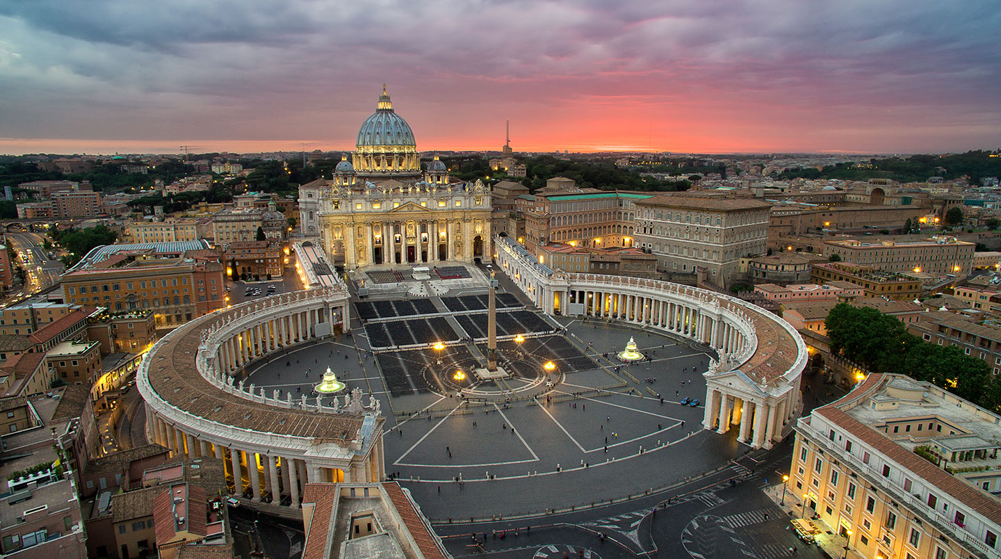 (A spectacular view from above, as the sky lights up behind The Vatican in Rome.)