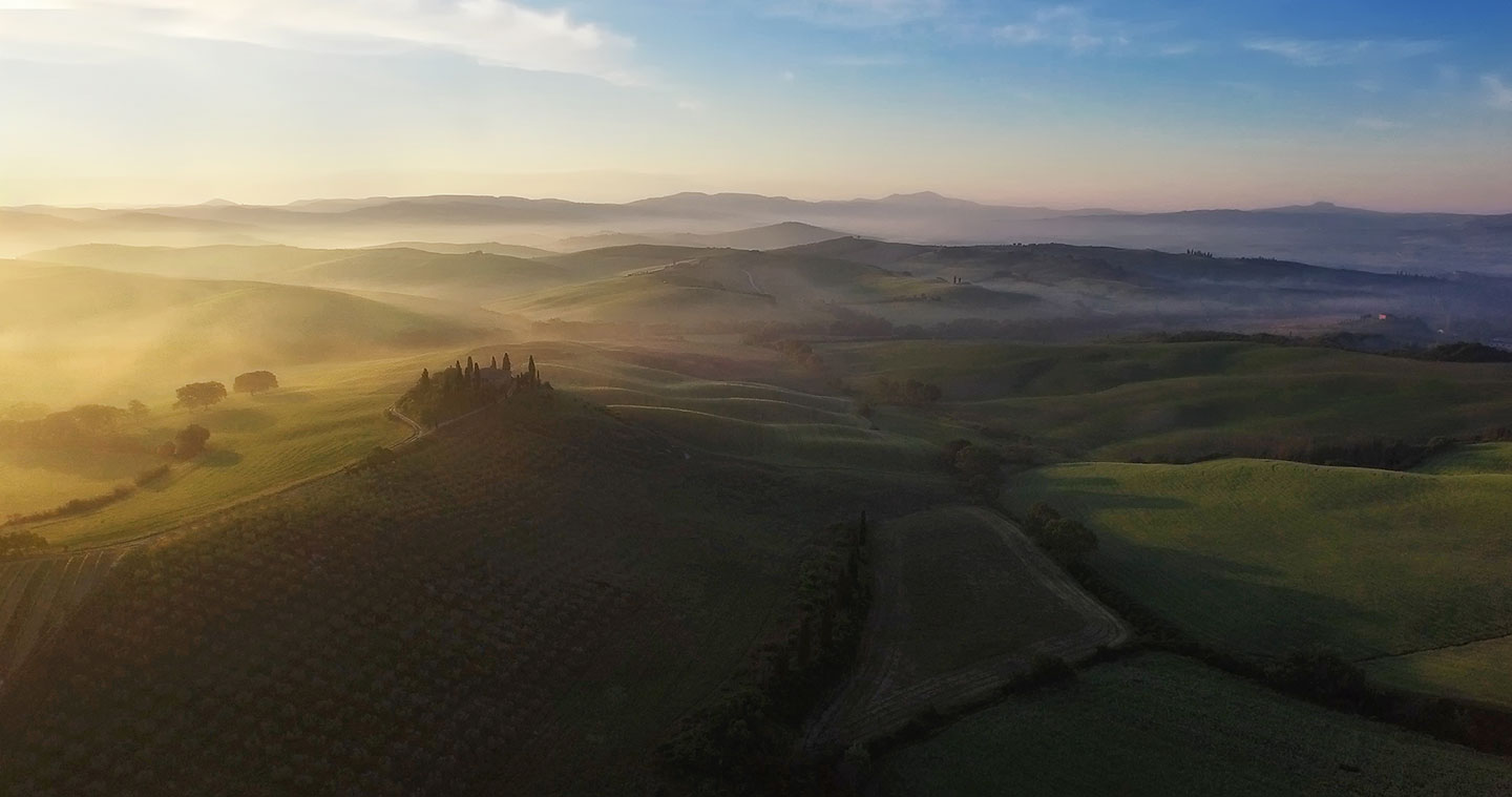 (Early morning light engulfs the rolling hills of Tuscany.)