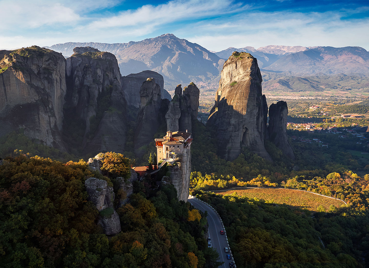 (Morning light streams through the valley and illuminates a lonely monastery in Meteora Greece.)